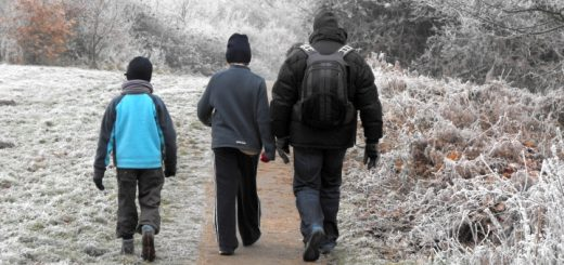 Family group walking in frosty countryside. Photograph by Tlst